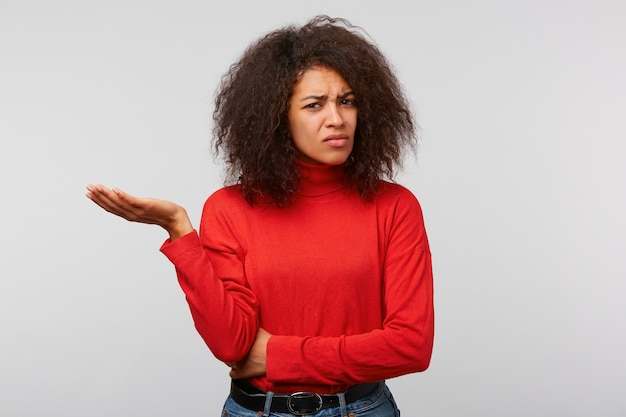 The woman with curly afro hair standing with folded hand and one palm raised, looks skeptically