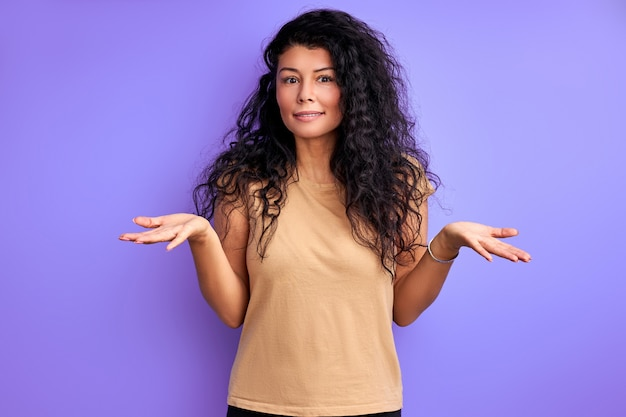 Woman with curly black hair shrugging misunderstanding, portrait of emotional female isolated