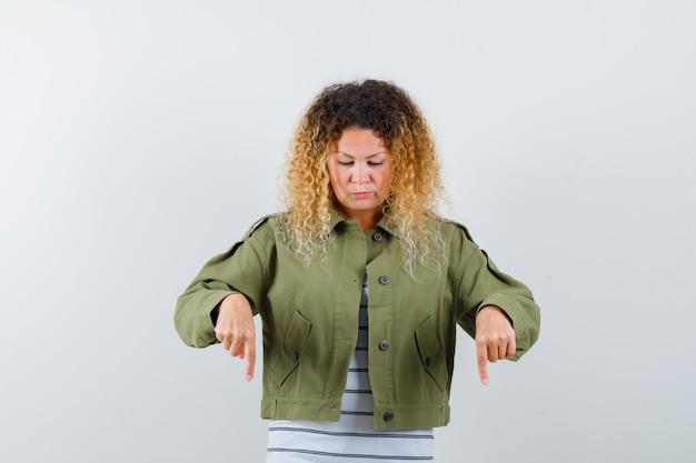 緑のジャケットを着た巻き毛のブロンドの髪の女性が下を向いて不思議に見える、正面図。