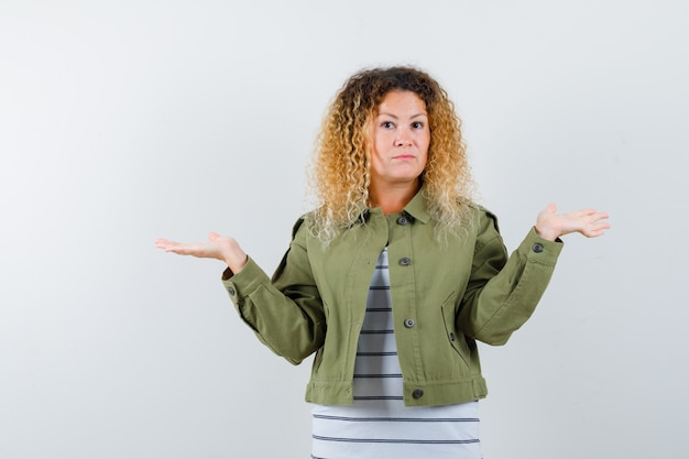 無力なジェスチャーを示し、優柔不断に見える緑色のジャケットの巻き毛のブロンドの髪の女性、正面図。