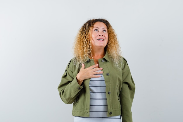 Woman with curly blonde hair keeping hand on chest in green jacket and looking thankful. front view.