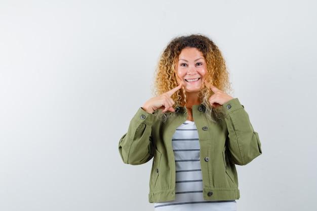 녹색 재킷에 그녀의 미소를 가리키고 쾌활한 찾고 곱슬 금발 머리를 가진 여자. 전면보기.