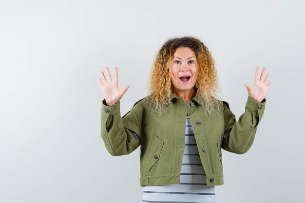 緑のジャケットで降伏のジェスチャーで手のひらを示し、不思議に見える、正面図の巻き毛のブロンドの髪の女性。
