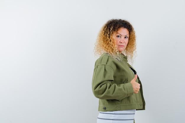 緑のジャケットに親指を立てて自信を持って見える巻き毛のブロンドの髪の女性。正面図。