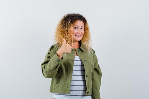 Женщина с вьющимися светлыми волосами показывает большой палец вверх в зеленой куртке и выглядит веселой. передний план.