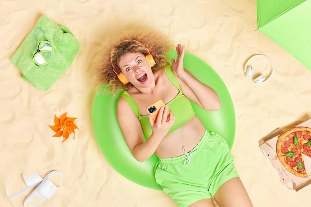 곱슬곱슬한 머리를 한 여성이 즐거운 소식을 전하며 여름 옷을 입은 현대적인 스마트폰을 들고 해변에서 좋은 휴식을 취하고 있다