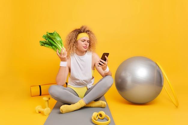 Женщина с вьющимися густыми волосами держит смартфон, недовольна чем-то, держит зеленые овощи, сидит, скрестив ноги на фитнес-коврике.