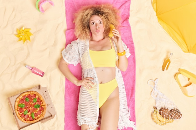 Woman with curly bushy hair keeps banana near ear as of telephone dressed in bathing suit lies on towel spends summer holidays at seaside surrounded by beach acessories
