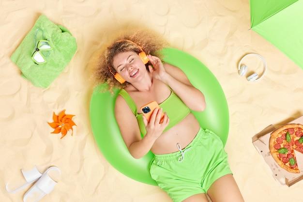 巻き毛のふさふさした髪の女性は、プレイリストからお気に入りの音楽を聴きます夏服に身を包んだ現代の携帯電話を持っていますビーチで日光浴は膨らんだ水泳に横たわっています。