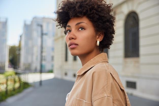 La donna con i capelli ricci e folti guarda in lontananza ha un aspetto affascinante vestita con una giacca beige passeggia all'aperto spazio vuoto per la copia