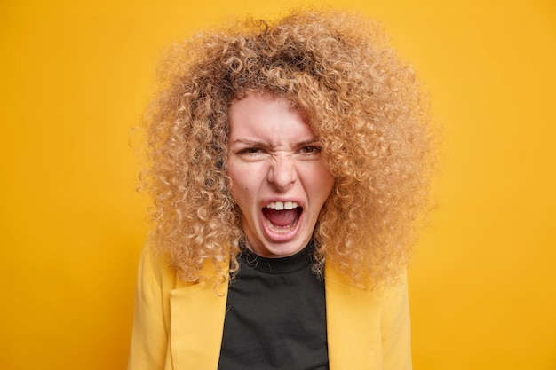 Woman with curly bushy hair screams angrily has quarrel expresses negative emotions wears formal clothing