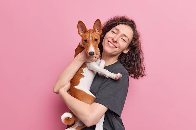 Женщина с вьющимися темными волосами несет свою собаку басенджи проводить время вместе иметь дружеские отношения иметь прогулку позу на розовом
