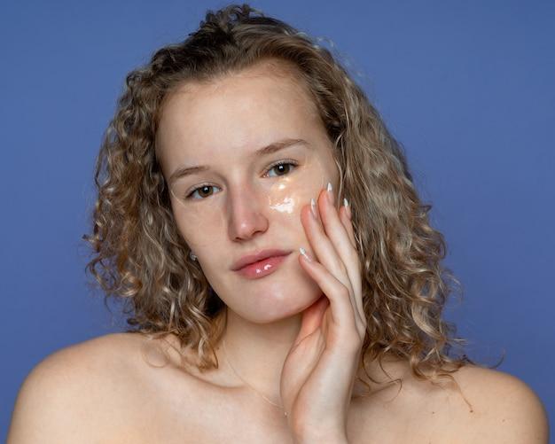 Женщина с вьющимися волосами и открытыми плечами, надменная и касающаяся лица рукой, золотые пятна под глазами, уход за лицом на синей стене