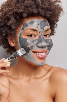 巻き毛の女性は、裸の体の笑顔で化粧ブラシスタンド付きの美容クレイマスクを適用し、屋内で優しくポーズします。スキンケアの贅沢と健康
