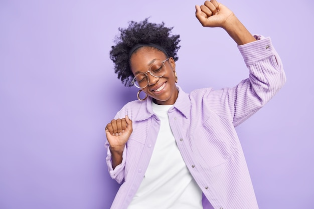 Woman with curly hair dances carefree raises hands up keeps eyes closed tilts head wears spectacles and shirt isolated on purple wall moves on dance floor