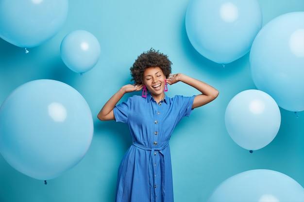유행 드레스를 입은 곱슬 머리를 가진 여자는 음악을 즐기고 팽창 된 풍선 주위에 파티 포즈는 파란색에 고립 된 축제 무스가 있습니다