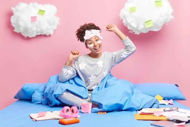 Женщина с вьющимися волосами, одетая в пижаму и маску для сна, держит руки поднятыми, в хорошем настроении сидит, скрестив ноги на удобной кровати, делает документы, составляет список дел на красочных наклейках