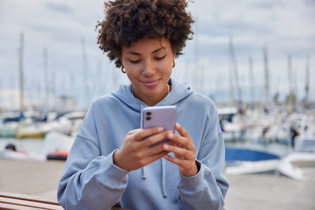 Woman with curly hair dressed in sweatshirt holds mobile phone has long awaited vacation walks in sea port near yachts and ports enjoys summer travel checks notification