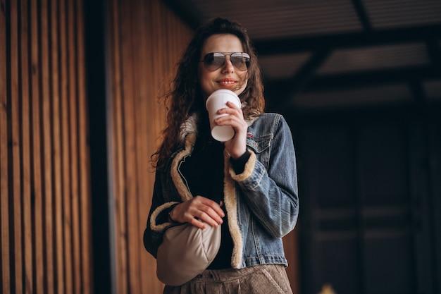 コーヒーを飲んで巻き毛を持つ女性
