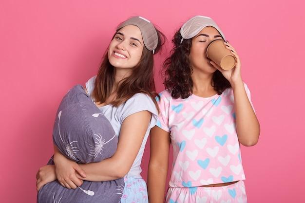 閉じた幸せな笑顔を持つ彼女の友人がカメラを見て、枕、パジャマパーティー、友人が頭に目隠しを着用し、ピンクの背景に孤立してポーズをとっている間、巻き毛の女性がコーヒーを飲む