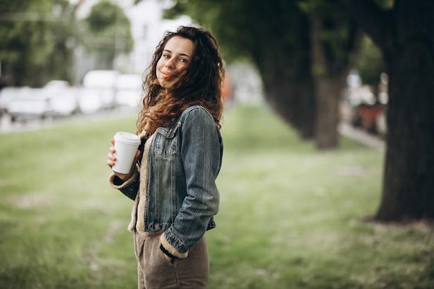 コーヒーを飲みながら巻き毛を持つ女性