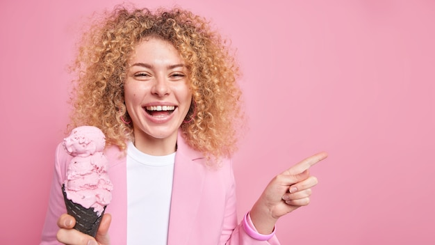 Woman with curly hair eats delicious ice cream in waffle points away on blank space presents summer product wears pink jacket