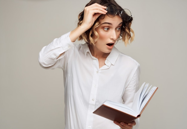 Woman with curly hair in glasses with a book in her hands work by studio. high quality photo