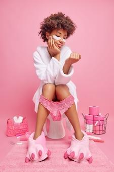 Donna con i capelli ricci ha disturbi digestivi si siede sul water in bagno applica cerotti sotto gli occhi indossa accappatoio bianco pantofole mutandine sulle gambe isolate sul muro rosa