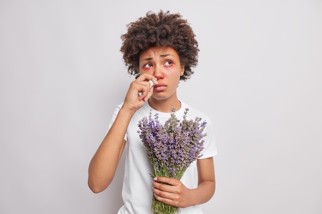 Woman with curly hair has inflammation of eyes runny nose sprays nasal aerosol being allergic to lavender looks sadly somewhere poses on white