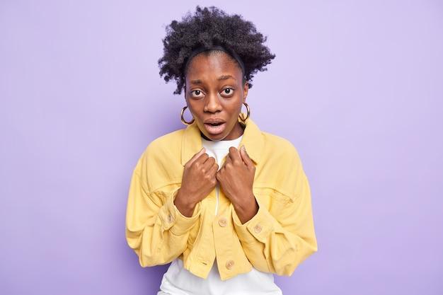 巻き毛の女性は息を止めて息を呑む屋内で唖然と口を開けたまま黄色のジャケットを着て紫で隔離
