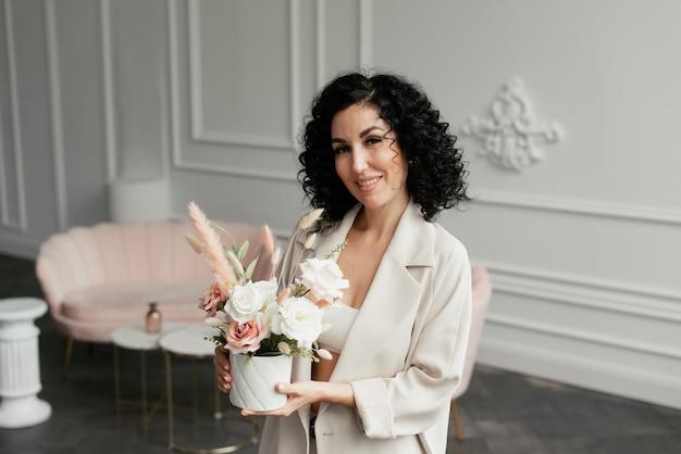 スーツを着た巻き毛の女性が花束を手に持って笑う