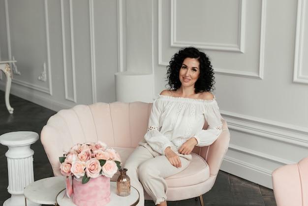 白いブラウスに巻き毛の女性は、花の花束の横にあるピンクのソファに座っています