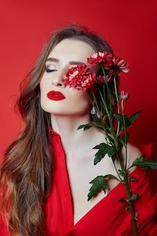 赤いドレスと花の手で巻き毛の女性