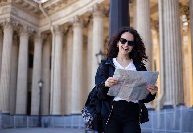 手で市内地図とサングラスの巻き毛を持つ女性