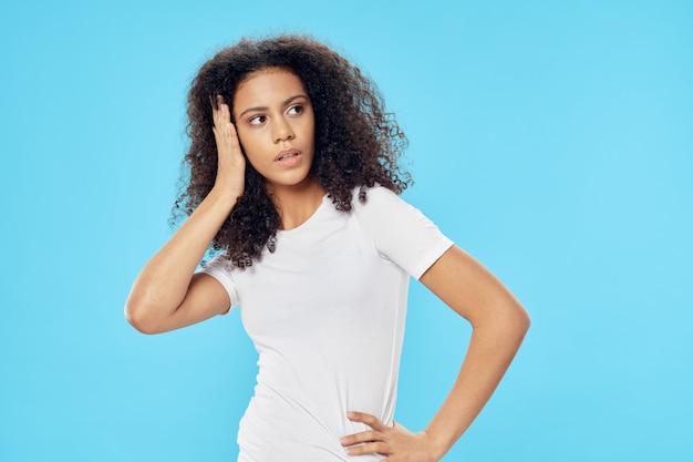 흰색 tshirt 라이프 스타일 파란색 배경에 곱슬 머리를 가진 여자