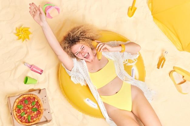 巻き毛の女性はバナナを耳の近くに保ち、電話で話しているふりをして腕を上げたまま黄色いビキニを着て海辺の砂浜で日光浴をします