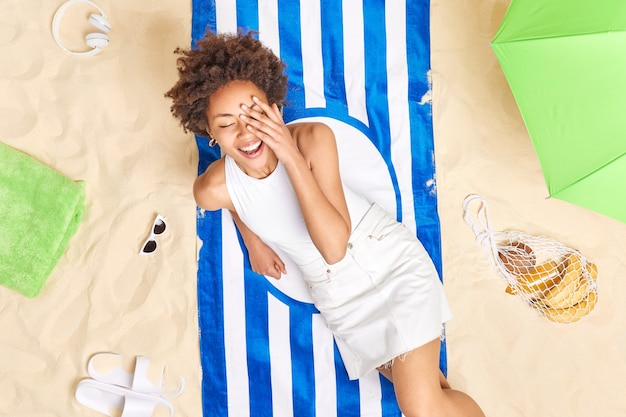 Woman with curly hair keeps hand on face smiles gladfully dressed in white t shirt and skirt poses on striped towel enjoys summer time spends all day at beach