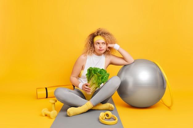 곱슬머리를 한 여성이 스위스 공을 들고 녹색 채소를 들고 피트니스 매트에 다리를 꼬고 앉아 핏볼 훌라후프 덤벨 카레맛으로 둘러싸인 훈련 후 피곤함을 느낀다