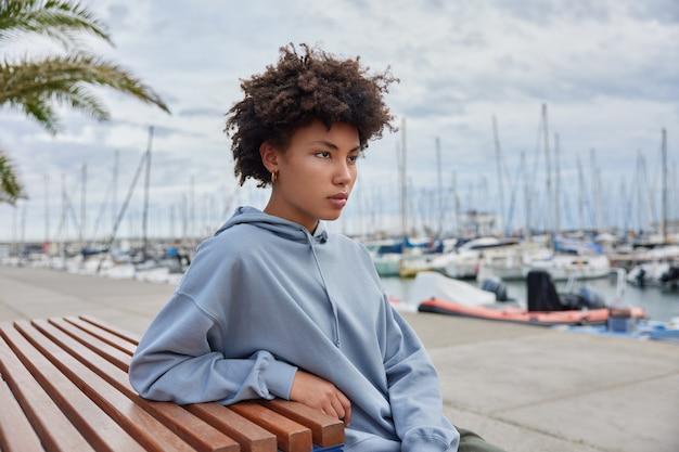 巻き毛の女性は、海の港の桟橋でカジュアルなパーカーのポーズに身を包んだ距離を注意深く見ています休暇中の美しい景色を賞賛します