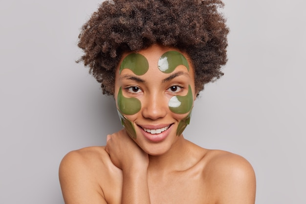 Woman with curly hair looks directly at camera applies hydrogel green patches on face for rejuvenation has well cared body healthy skin poses alone