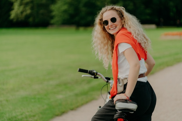 Woman with curly hair, looks from back, stops during riding bicycle