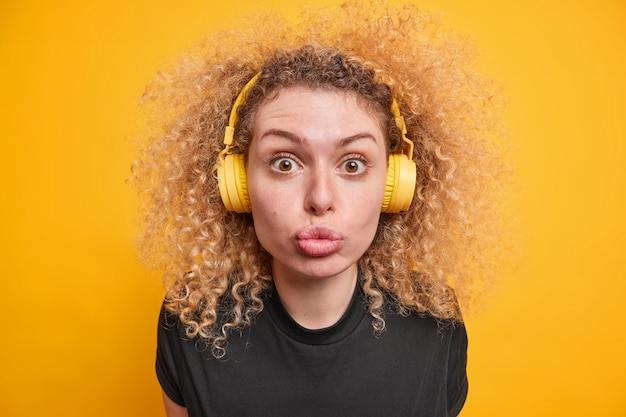 Woman with curly hair looks with flirty expression at camera keeps lips folded listens music via headphones enjoys spare time dressed in casual t shirt poses