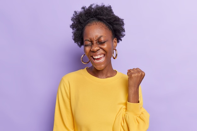 Woman with curly hair makes yes gesture feels like winner raises fist wears yellow jumper and earrings isolated on purple