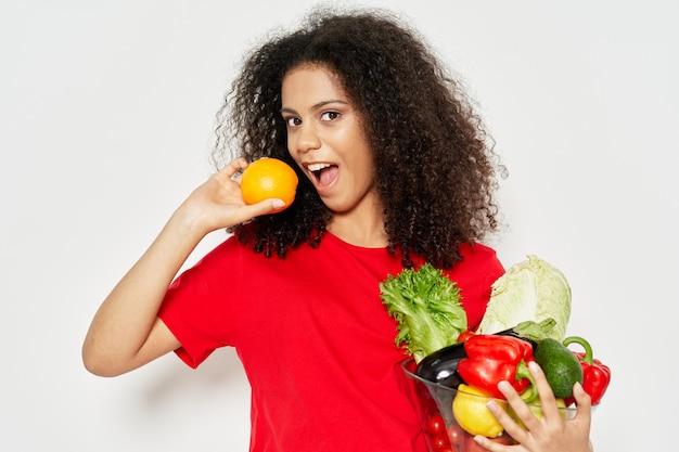 野菜の健康食品と巻き毛のプレートを持つ女性