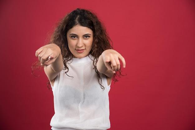 赤のカメラに 2 本の指を指す巻き毛の女性。