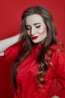 Женщина с вьющимися волосами красное платье на красном фоне