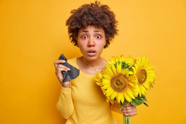 巻き毛の赤い腫れた目を持つ女性は、鮮やかな黄色で屋内でポーズをとっているヒマワリに対するアレルギーのためにナプキンのくしゃみを保持します