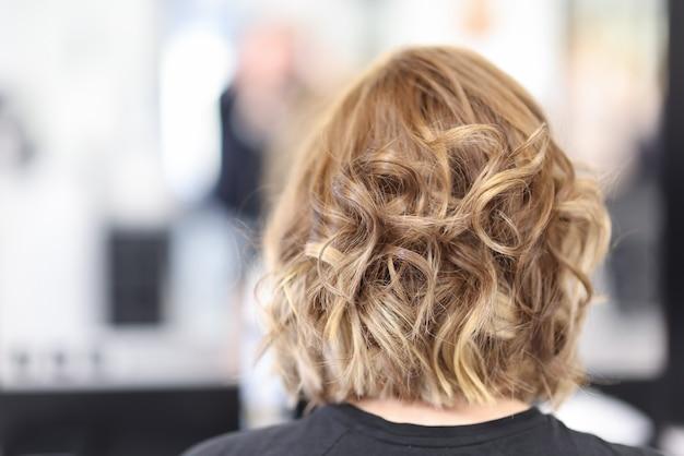 巻き毛を持つ女性は、ビューティーサロンの背面図に座っています。