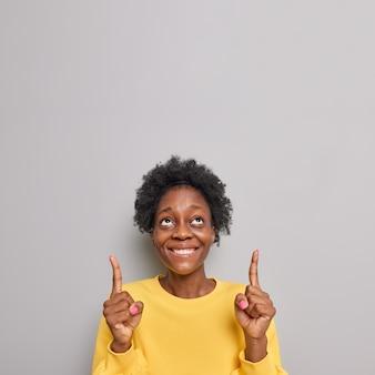 곱슬 머리 미소를 가진 여자와 낙관적 인 모습은 회색에 고립 된 위쪽으로 검지 손가락을 가리키는 광고를 보여줍니다