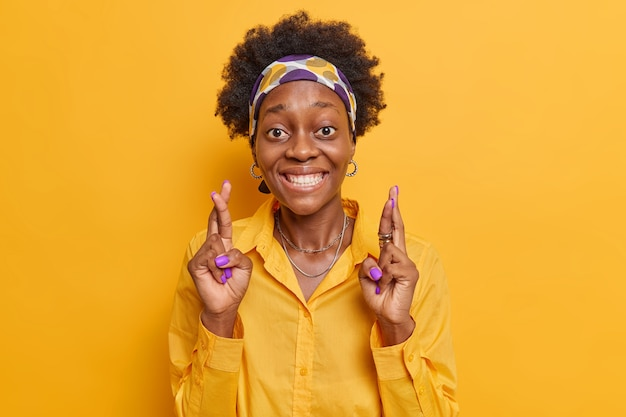 Woman with curly hair smiles broadly keeps fingers crossed believes in good luck wears headband and casual shirt isolated on vivid yellow